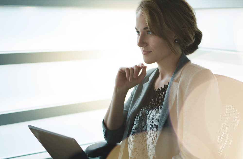 Woman writing compelling content in front of a window.