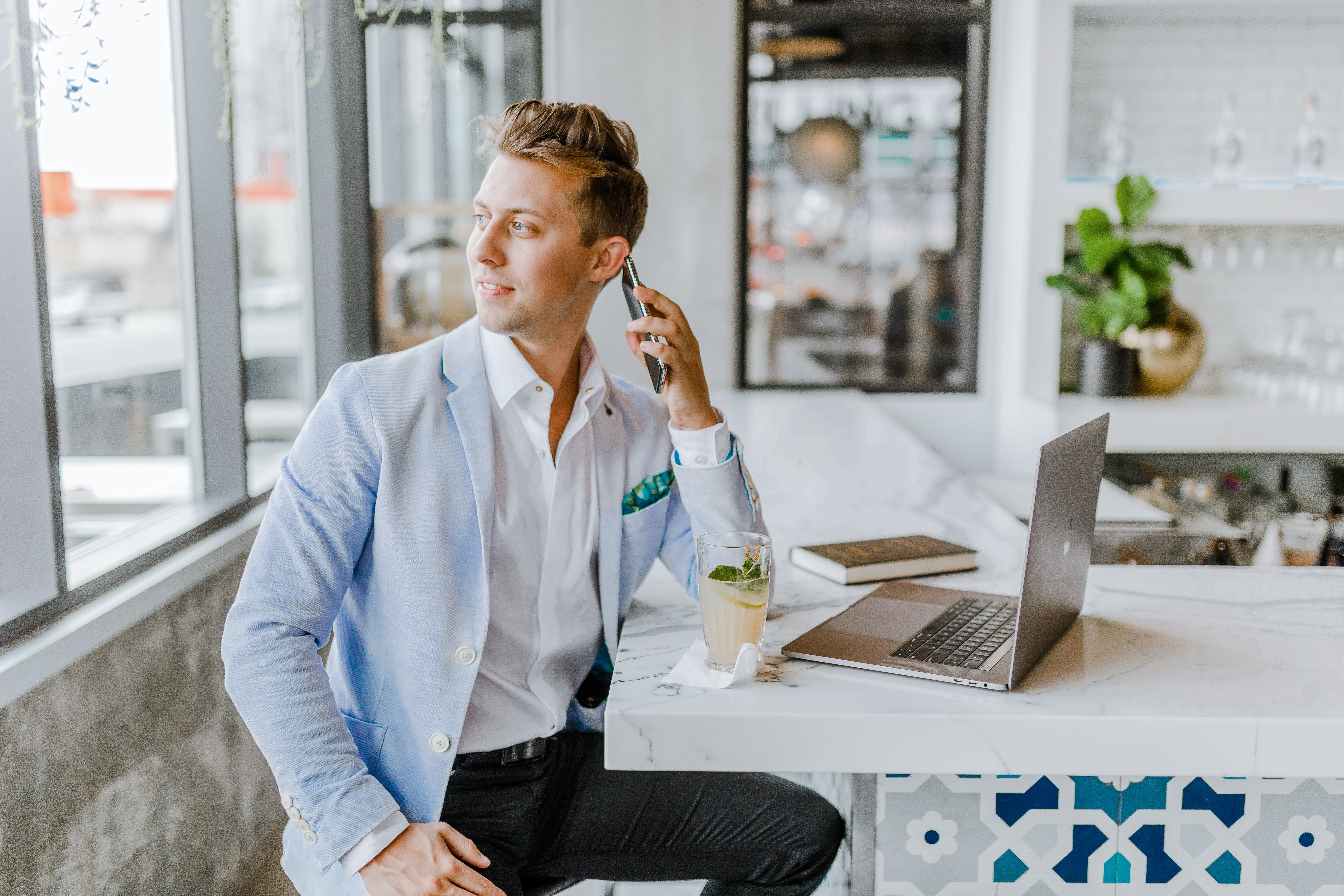 Man looking out window on the phone while sitting at his office desk